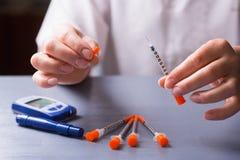 Manos pacientes femeninas que sostienen la jeringuilla abierta de la insulina, glucometer en la tabla imágenes de archivo libres de regalías