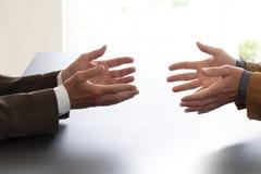 Manos a partir de dos hombres de negocios en la conversación por un escritorio Negocio de negociación o una entrevista de trabajo imagenes de archivo