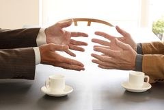 Manos a partir de dos hombres de negocios en la conversación por un escritorio Dos tazas de caf? en la tabla Negocio de negociaci imagen de archivo libre de regalías