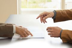 Manos a partir de dos hombres de negocios en la conversación por un escritorio Uno que señala en papeles Negocio de negociación o foto de archivo