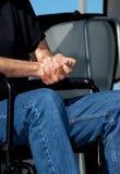 Manos plegables en un sillón de ruedas Fotos de archivo libres de regalías