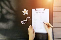 Manos, pluma y solicitud de visado planas de la mujer de la endecha para el viaje, retrato de la luz del sol con las gafas de sol Fotos de archivo