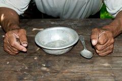 Manos pobres del ` s del viejo hombre y cuenco vacío en fondo de madera Un hombre hambriento enojado aprieta sus manos en los puñ imagen de archivo libre de regalías