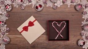 Manos que abren el corazón que revela del regalo de Navidad que forma los bastones de caramelo almacen de video