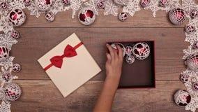 Manos que abren el manojo que revela del regalo de Navidad de chucherías de Navidad metrajes