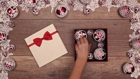 Manos que abren el manojo que revela del regalo de Navidad de chucherías hecha a ganchillos de Navidad almacen de metraje de vídeo