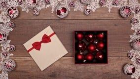 Manos que abren el manojo que revela del regalo de Navidad de chucherías rojas de Navidad metrajes