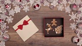 Manos que abren el regalo de Navidad con las galletas del pan de jengibre dentro almacen de metraje de vídeo