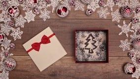 Manos que abren el regalo de Navidad que revela el árbol de Navidad metrajes