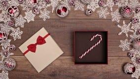 Manos que abren el regalo de Navidad que revela un regalo del bastón de caramelo almacen de video