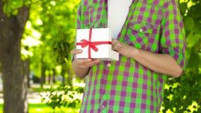 Manos que abren el regalo en parque almacen de metraje de vídeo