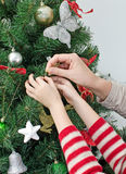 Manos que adornan el árbol de navidad Fotografía de archivo libre de regalías