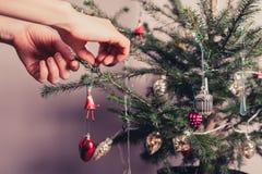 Manos que adornan el árbol de navidad Foto de archivo libre de regalías