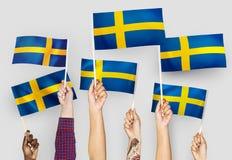 Manos que agitan las banderas de Suecia imagen de archivo libre de regalías