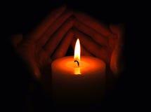 Manos que ahuecan la llama de vela Fotografía de archivo libre de regalías