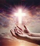Manos que alcanzan hacia fuera con la cruz del crucifijo en cielo de la puesta del sol Imagenes de archivo
