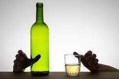 Manos que alcanzan para un vidrio y una botella Fotografía de archivo libre de regalías