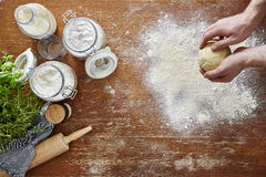 Manos que amasan utilidades de la harina y de la cocina de la pasta de las pastas en espacio de trabajo de madera Imagen de archivo libre de regalías