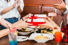 Manos que aplauden del grupo de personas para felicitarse para el regalo o las recompensas de cumpleaños durante cena fotografía de archivo
