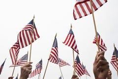 Manos que aumentan banderas americanas Imágenes de archivo libres de regalías