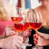 Manos que aumentan los vidrios de vino rojo sabroso Fotografía de archivo libre de regalías