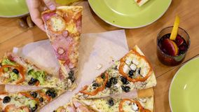 Manos que cogen rebanadas de la pizza en un cierre de la tabla metrajes