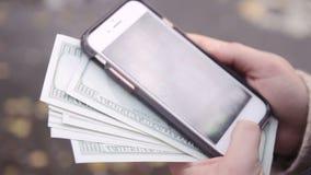 Manos que compran mercancías de Internet en su smartphone con su tarjeta de crédito metrajes