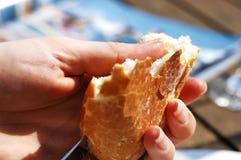 Manos que cortan el pan imagen de archivo