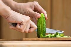 Manos que cortan el pepino en la tabla de cortar de madera Foto de archivo libre de regalías