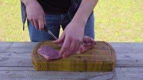 Manos que cortan la carne usando un cuchillo en un exterior superficial de madera almacen de video
