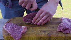 Manos que cortan la carne usando un cuchillo en un exterior superficial de madera metrajes