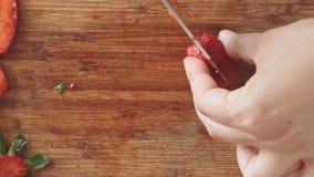Manos que cortan la fresa con el cuchillo de cocina almacen de metraje de vídeo