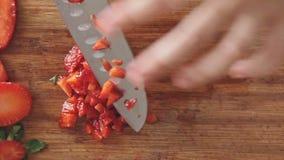 Manos que cortan la fresa con el cuchillo de cocina metrajes
