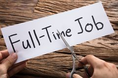 Manos que cortan las tijeras a tiempo completo de Job Words On Paper With imagenes de archivo