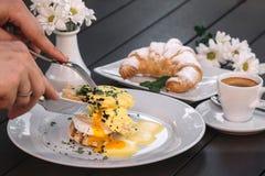 Manos que cortan los huevos Benedicto Fotografía de archivo