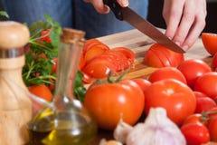 Manos que cortan los tomates en la tabla Fotos de archivo libres de regalías