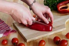 Manos que cortan una pimienta Foto de archivo