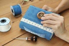 Manos que cosen el botón en el diario azul hecho a mano de la mezclilla fotografía de archivo libre de regalías