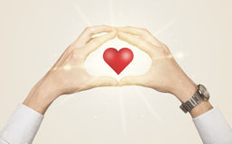 Manos que crean una forma con el corazón brillante Foto de archivo libre de regalías