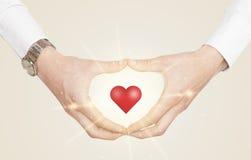 Manos que crean una forma con el corazón brillante Fotos de archivo