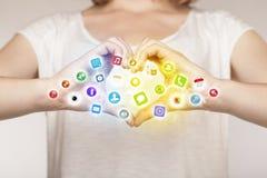 Manos que crean una forma con los iconos móviles del app Imagen de archivo