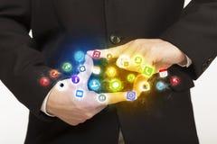 Manos que crean una forma con los iconos móviles del app Fotografía de archivo