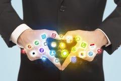 Manos que crean una forma con los iconos móviles del app Imagen de archivo libre de regalías