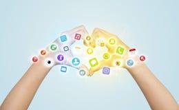 Manos que crean una forma con los iconos móviles del app Imagenes de archivo