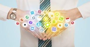 Manos que crean una forma con los iconos móviles del app Imágenes de archivo libres de regalías