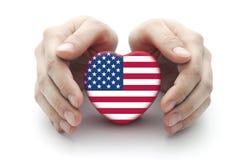 Manos que cubren el corazón de los E.E.U.U. Imagen de archivo