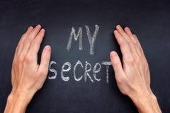 Manos que cubren para arriba palabras mi secreto foto de archivo libre de regalías