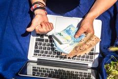 Manos que cuentan billetes de banco en un ordenador port?til foto de archivo