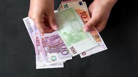Manos que cuentan las cuentas de los euros de diversos valores Dinero euro del efectivo almacen de video