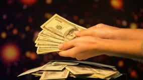 Manos que cuentan los dólares contra fondo chispeante, ganancias de la lotería, riqueza metrajes